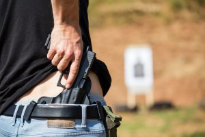 Man drawing handgun from a concealed holster at an outdoor gun range